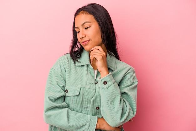 Młoda kobieta łacińskiej na białym tle na różowym tle patrząc z boku z wyrazem wątpliwości i sceptyczny.