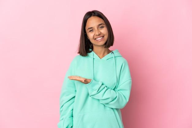 Młoda kobieta łacińskiej na białym tle na różowym tle, prezentując pomysł, patrząc w kierunku uśmiechniętym