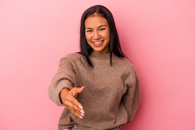 Młoda kobieta łacińskiej na białym tle na różowym tle rozciągania ręki w aparacie w geście pozdrowienia.