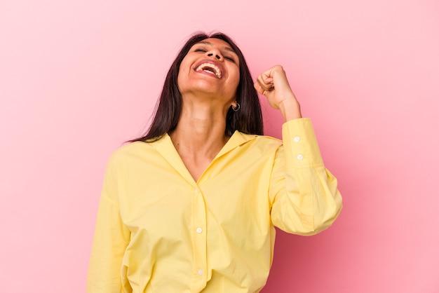 Młoda kobieta łacińskiej na białym tle na różowym tle świętuje zwycięstwo, pasję i entuzjazm, szczęśliwy wyraz.