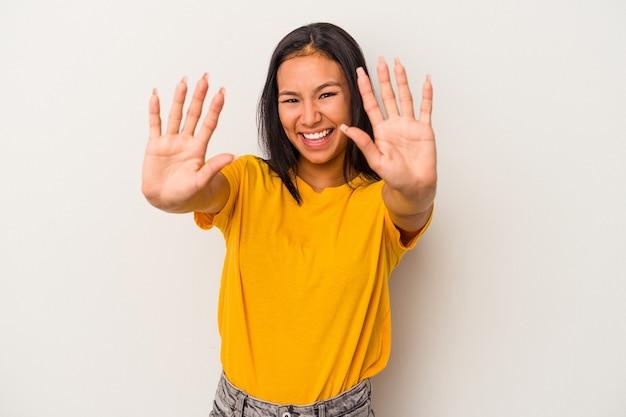 Młoda kobieta łacińskiej na białym tle pokazuje numer dziesięć z rękami.