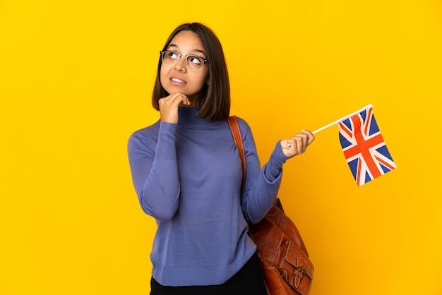 Młoda kobieta łacińskiej posiadających flagę zjednoczonego królestwa na białym tle na żółtym tle patrząc w górę podczas uśmiechu