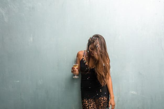 Młoda kobieta łacińskiej świętuje nowy rok lub wydarzenie. podekscytowany i szczęśliwy, trzymając butelkę szampana i kubek.