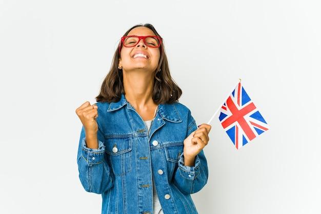 Młoda kobieta łacińskiej trzyma angielską flagę na białym tle na białej ścianie świętuje zwycięstwo, pasję i entuzjazm, szczęśliwy wyraz.