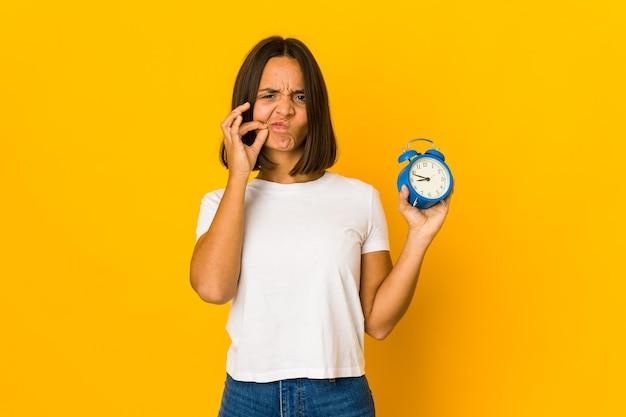 Młoda kobieta łacińskiej trzyma budzik