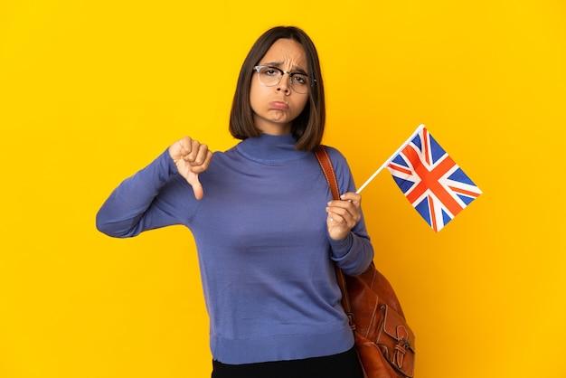Młoda kobieta łacińskiej trzyma flagę zjednoczonego królestwa na białym tle na żółtej ścianie, dzięki czemu znak dobry-zły. niezdecydowany między tak lub nie