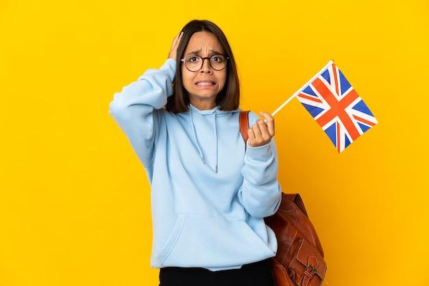 Młoda kobieta łacińskiej trzyma flagę zjednoczonego królestwa na białym tle na żółtej ścianie, robi nerwowy gest