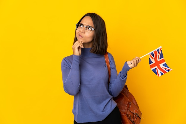 Młoda kobieta łacińskiej trzyma flagę zjednoczonego królestwa na białym tle na żółtym tle i patrząc w górę