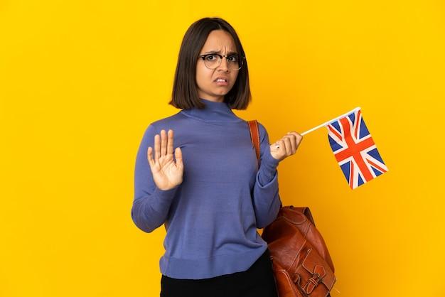 Młoda kobieta łacińskiej trzyma flagę zjednoczonego królestwa na białym tle na żółtym tle nerwowy rozciąganie rąk do przodu
