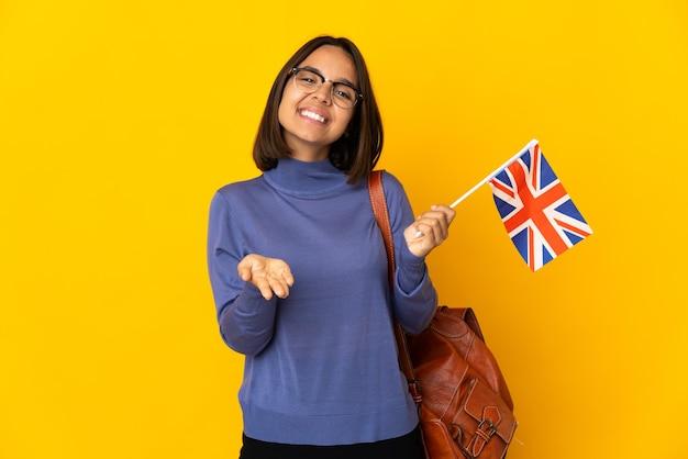 Młoda kobieta łacińskiej trzyma flagę zjednoczonego królestwa na białym tle na żółtym tle, trzymając copyspace wyimaginowany na dłoni, aby wstawić reklamę
