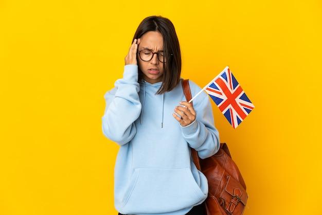 Młoda kobieta łacińskiej trzyma flagę zjednoczonego królestwa na białym tle na żółtym tle z bólem głowy
