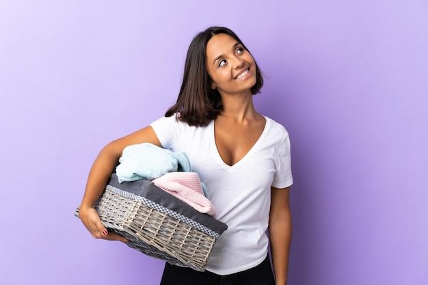 Młoda kobieta łacińskiej trzyma kosz na ubrania