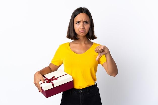 Młoda kobieta łacińskiej trzyma prezent