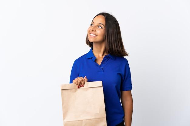 Młoda kobieta łacińskiej trzyma torbę na zakupy spożywcze na białym myśląc pomysł, patrząc w górę