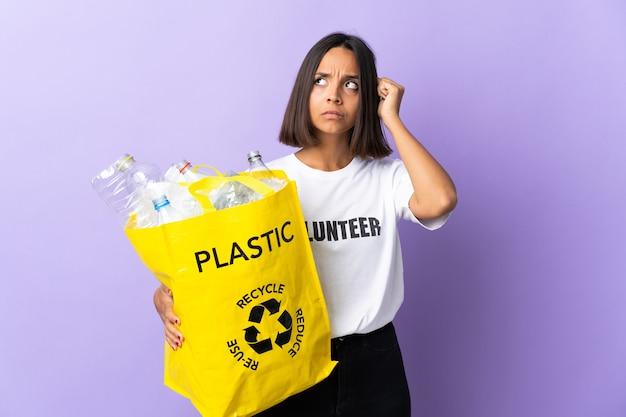 Młoda kobieta łacińskiej trzyma worek recyklingu pełnego papieru do recyklingu