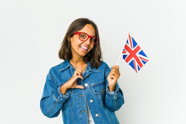 Młoda kobieta łacińskiej trzymając angielską flagę na białym tle uśmiechając się i przedstawiając kształt serca rękami.