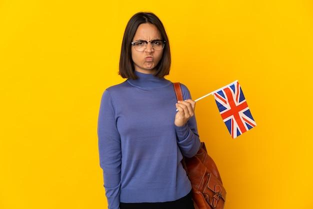 Młoda kobieta łacińskiej trzymając flagę zjednoczonego królestwa na białym tle