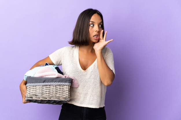 Młoda kobieta łacińskiej trzymając kosz z ubraniami na fioletowym tle szepcząc coś z gestem zaskoczenia, patrząc w bok