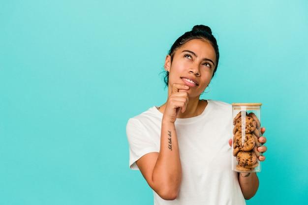 Młoda kobieta łacińskiej trzymając słoik ciasteczka na białym tle na niebieskim tle, patrząc w bok z wyrazem wątpliwości i sceptyczny.