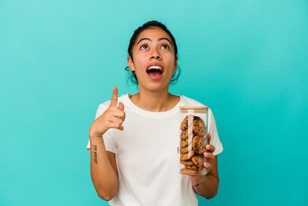 Młoda kobieta łacińskiej trzymając słoik ciasteczka na białym tle na niebieskim tle, wskazując do góry z otwartymi ustami.