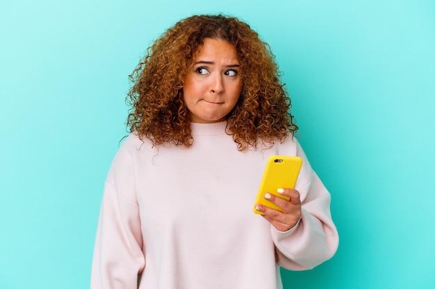 Młoda kobieta łacińskiej trzymając telefon komórkowy na białym tle na niebieskim tle zdezorientowana, wątpliwa i niepewna.