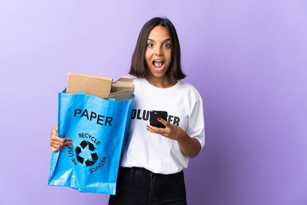 Młoda kobieta łacińskiej trzymająca worek recyklingu pełen papieru do recyklingu na białym tle na fioletowo zaskoczony i wysyłający wiadomość