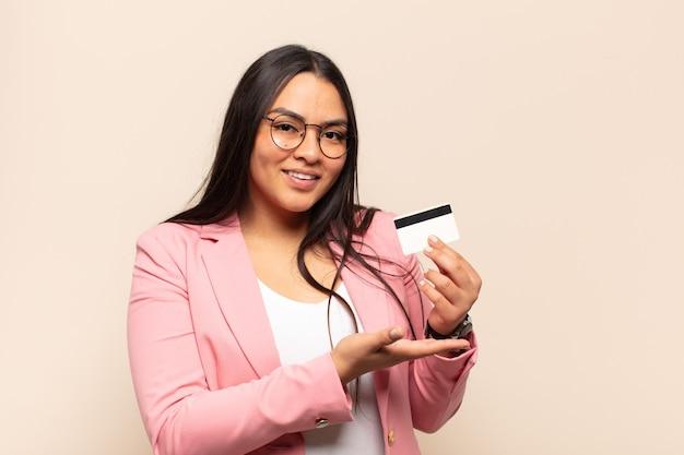Młoda kobieta łacińskiej uśmiecha się radośnie, czuje się szczęśliwy i pokazuje koncepcję w przestrzeni kopii z dłoni