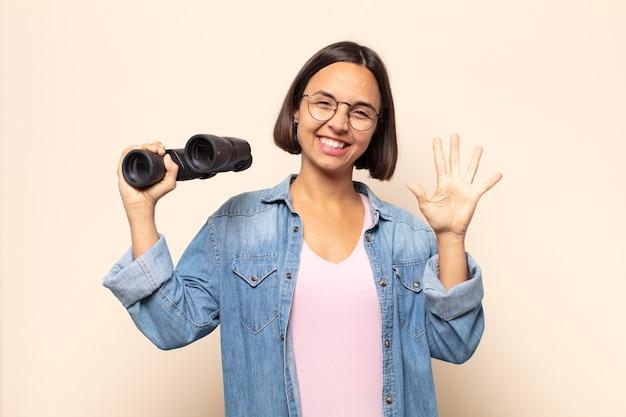 Młoda kobieta łacińskiej uśmiechnięta i wyglądająca przyjaźnie, pokazująca numer pięć lub piąty z ręką do przodu, odliczający w dół