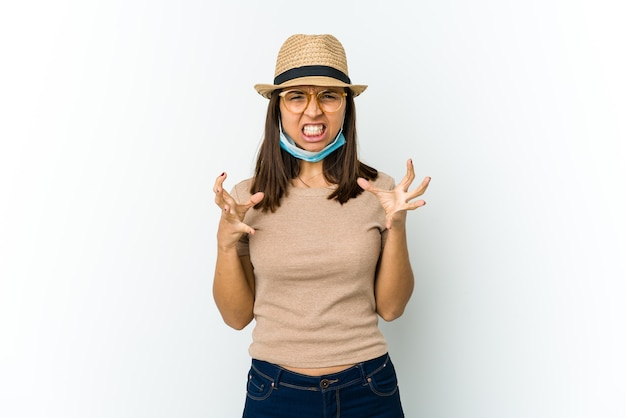 Młoda kobieta łacińskiej w kapeluszu i masce, aby chronić przed covid na białej ścianie zdenerwowany krzycząc z napiętymi rękami