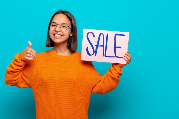 Młoda kobieta łacińskiej z tablicą sprzedaży