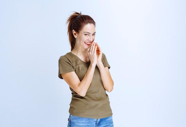 Młoda kobieta łącząca ręce i śniąca lub modląca się