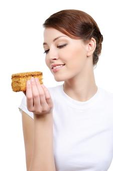 Młoda kobieta ładny jedzenie ciasta - na białym tle