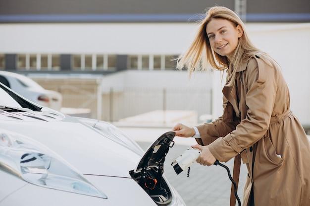 Młoda kobieta ładuje swój samochód elektryczny pistoletem ładującym