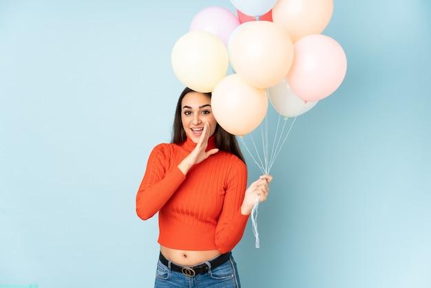 Młoda kobieta łapie wiele balonów na białym tle na niebieskiej ścianie coś szepcząc