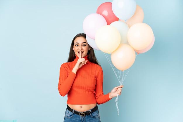 Młoda kobieta łapie wiele balonów na białym tle na niebieskiej ścianie robi gest ciszy