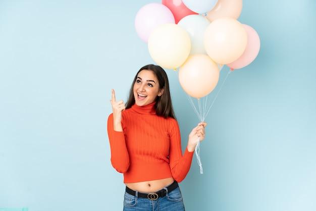 Młoda kobieta łapie wiele balonów na białym tle na niebieskiej ścianie, wskazując palcem wskazującym to świetny pomysł