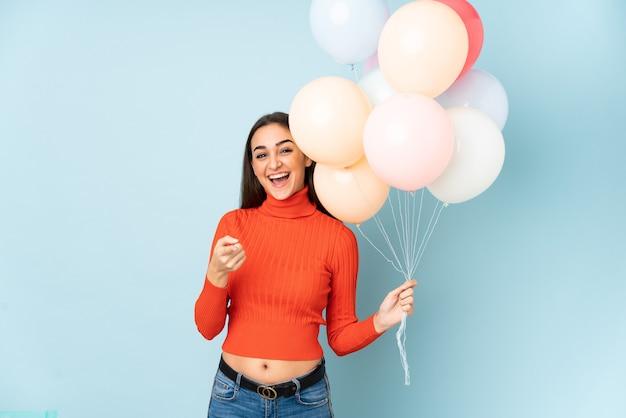 Młoda kobieta łapie wiele balonów na białym tle na niebieskiej ścianie wskazuje palcem na ciebie