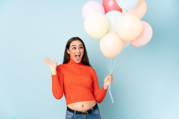 Młoda kobieta łapie wiele balonów na białym tle na niebieskiej ścianie z zaskoczeniem wyrazem twarzy