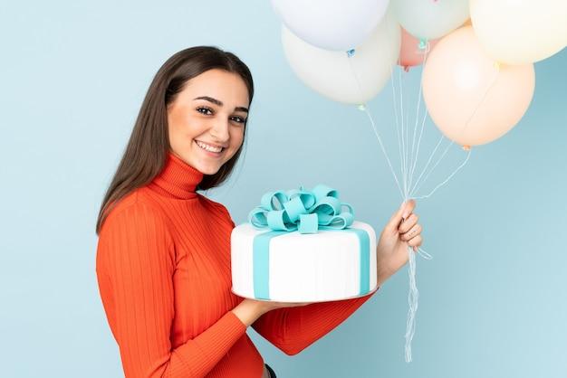 Młoda kobieta łapie wiele balonów na białym tle na niebieskiej ścianie