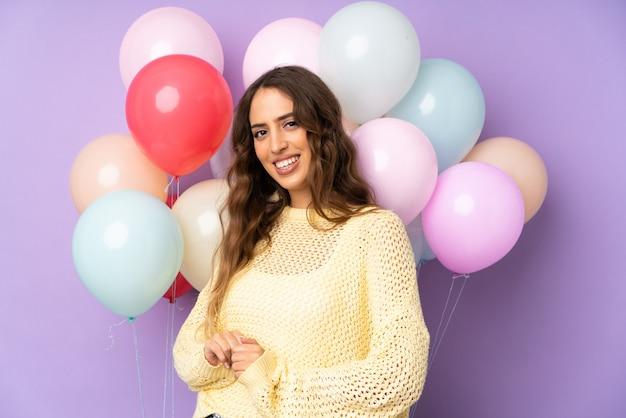 Młoda kobieta łapie wiele balony na purpury ścianie