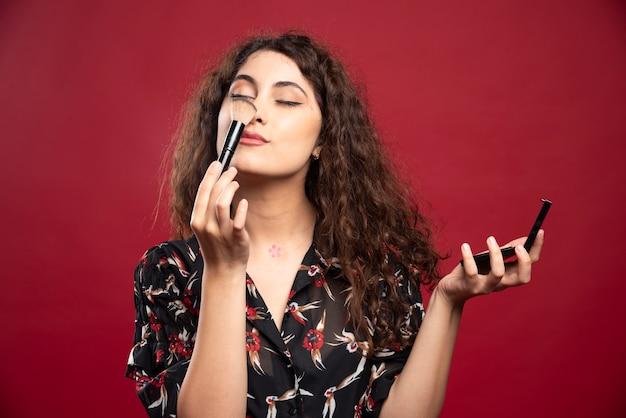 Młoda kobieta łaskocze nos pomponem.