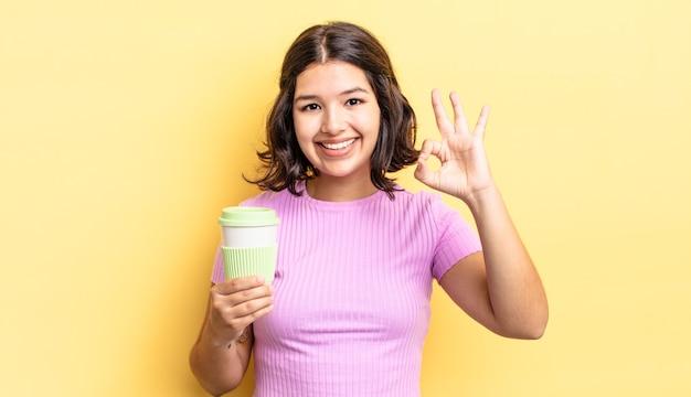 Młoda kobieta latynoska czuje się szczęśliwa, pokazując aprobatę w porządku gestem. koncepcja kawy na wynos