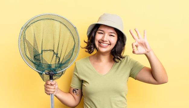 Młoda kobieta latynoska czuje się szczęśliwa, pokazując aprobatę w porządku gestem. koncepcja sieci rybackiej