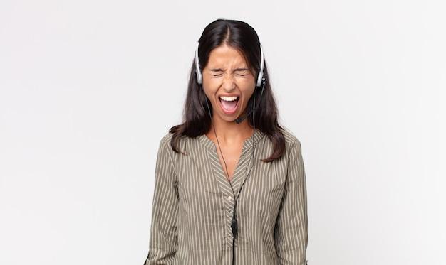 Młoda kobieta, latynoska, krzycząca agresywnie, wyglądająca na bardzo rozgniewaną z zestawem słuchawkowym. koncepcja telemarketingu