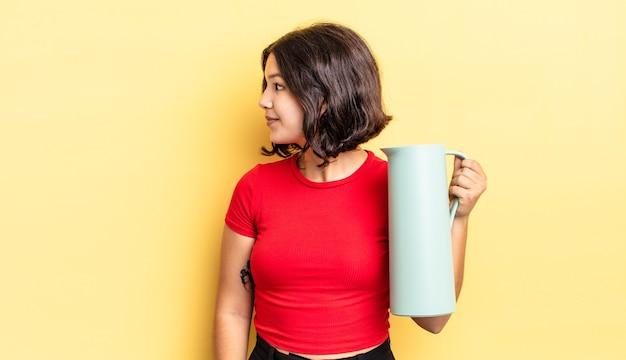 Młoda kobieta latynoska myśląca, wyobrażająca sobie lub marząca o widoku profilu. koncepcja termosu