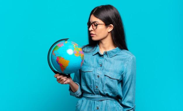 Młoda kobieta latynoska na widoku profilu, chcąc skopiować przestrzeń do przodu, myśląc, wyobrażając sobie lub marząc. koncepcja planety ziemi