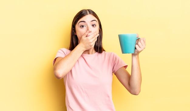 Młoda kobieta latynoska obejmujące usta rękami z szoku. koncepcja filiżanki kawy