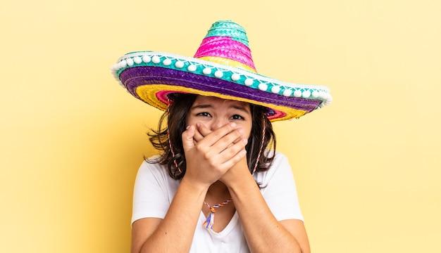 Młoda kobieta latynoska obejmujące usta rękami z szoku. koncepcja meksykańskiego kapelusza