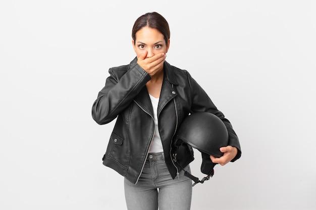 Młoda kobieta latynoska obejmujące usta rękami z szoku. koncepcja motocyklisty