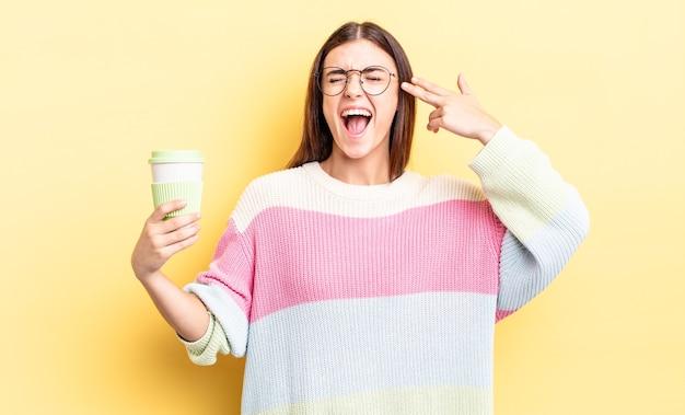 Młoda kobieta latynoska patrząc niezadowolony i zestresowany, gest samobójczy co pistolet znak. koncepcja kawy na wynos